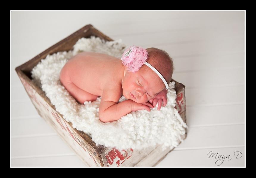 newborn in white crate