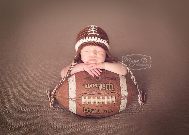 newborn boy with football hat